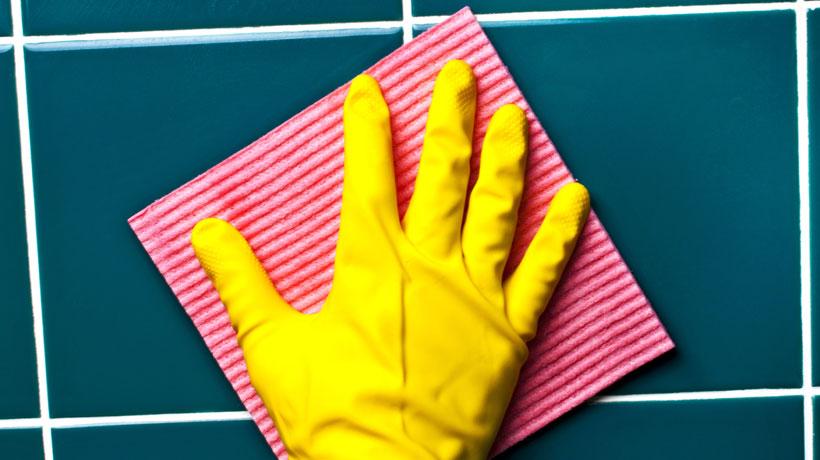 pessoa com luva amarela limpando azulejo