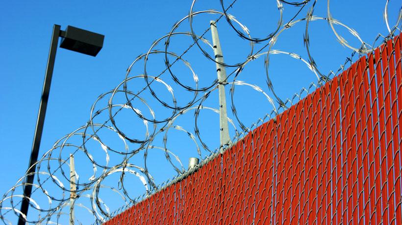 Muro com câmera e cerca de concertina