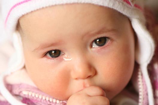 bebê chorando com a mão na boca