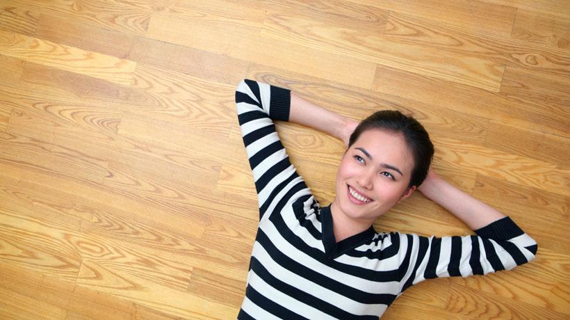 M/ulher deitada no chão com piso de madeira