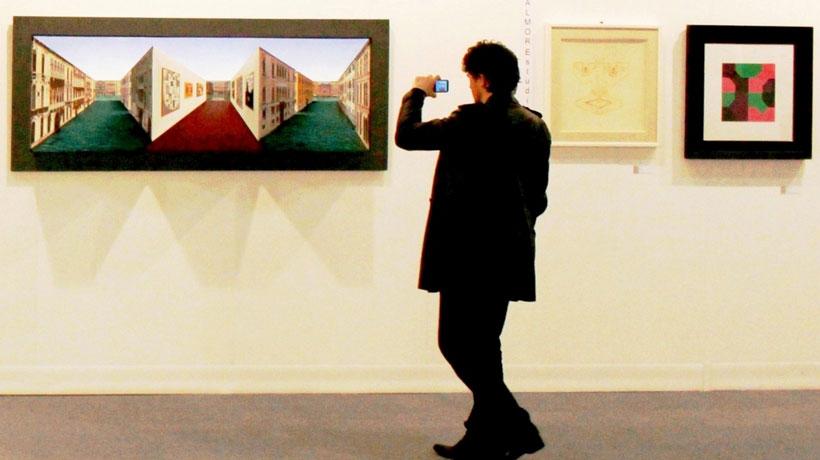 Homem fotografando obra em exposição de arte
