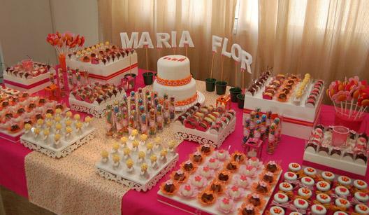 Mesa com doces, bolo e toalha de mesa rosa