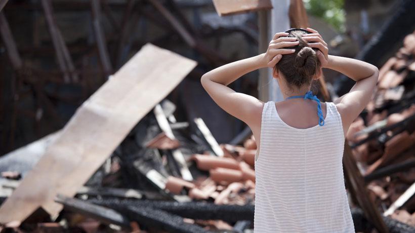 mulher olhando casa queimada
