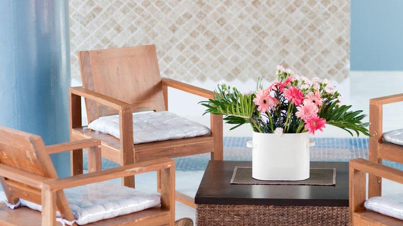 Mesa de centro com flor e cadeiras em volta