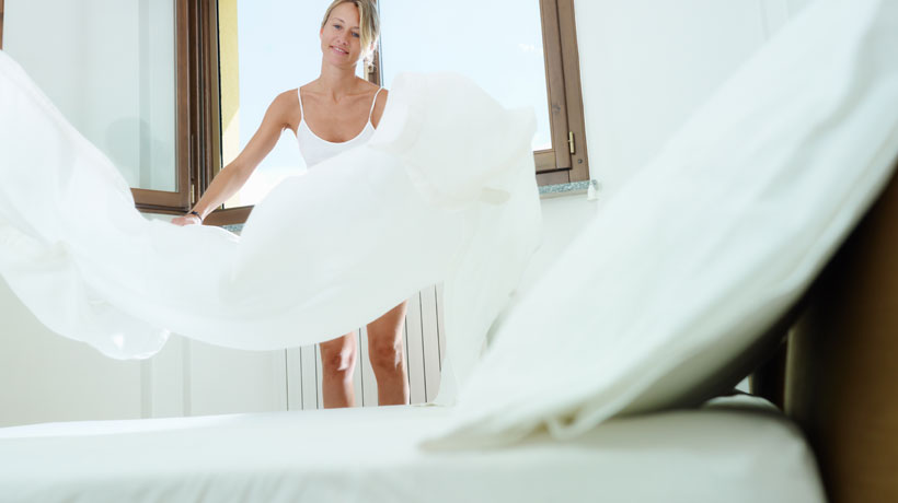 Mulher arrumando a cama