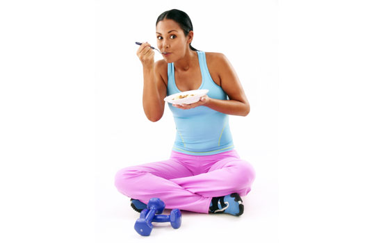 Mulher com roupas de academia comendo