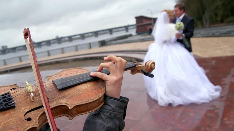 Homem tocando violino e casal de noivos
