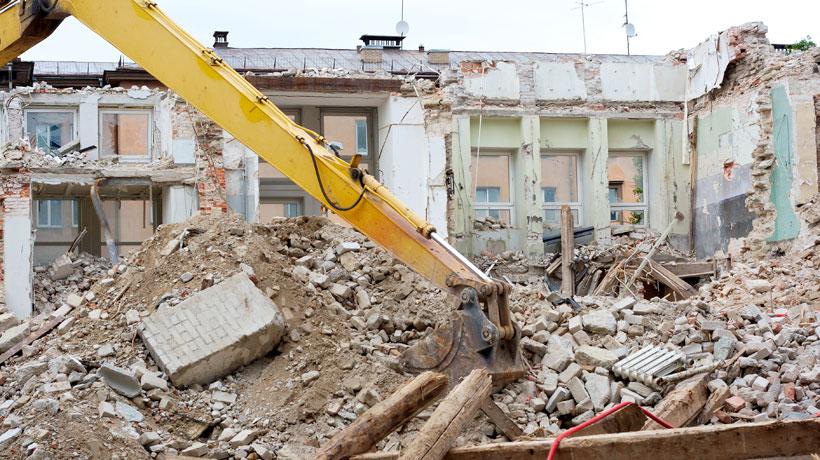 Máquina demolindo casa
