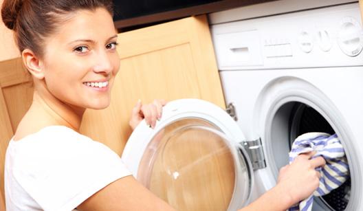 mulher colocando roupa na máquina