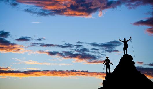Duas pessoas chegando no alto da montanha