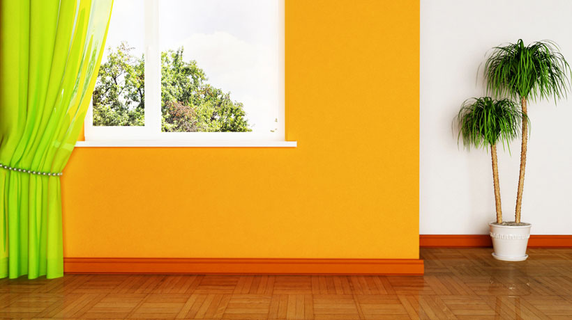 Piso de madeira, parede mostarda e rodapé laranja