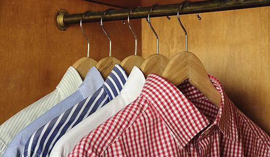 Camisas penduradas em cabides de madeira