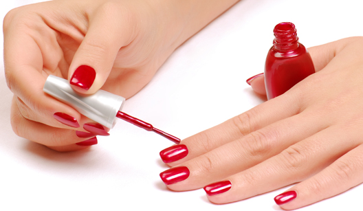 mulher passando esmalte vermelho