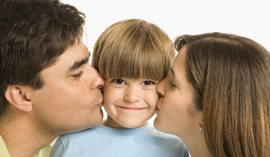 Pai e mãe beijando criança