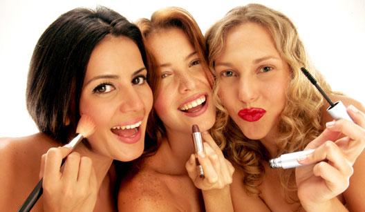 Três mulheres se maquiando juntas