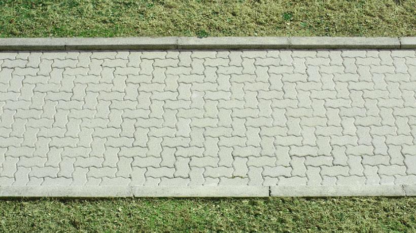 Calçada com grama e blocos de concreto