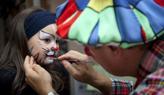 Adulto pintando o rosto de uma criança