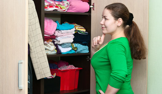 Mulher olhando para toalhas no armário