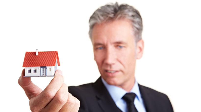 homem com casa em miniatura na mão