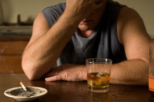homem triste fumando e bebendo