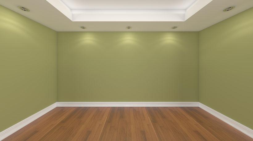 Piso de madeira, parede verde e rodapé branco