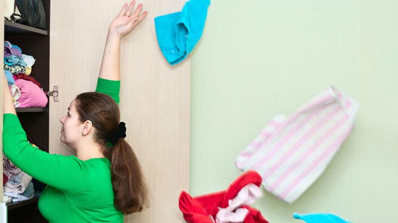 mulher jogando roupas fora do guarda-roupa